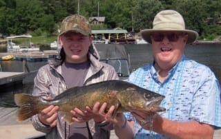 Photo of a Father and Son Holding a Giant Fish. Click Here to Learn more about our Ontario Vacations.